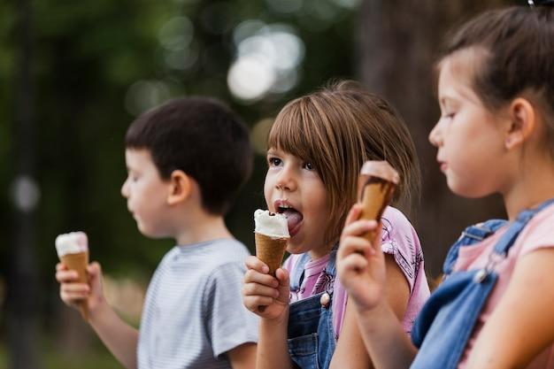 Niños pequeños disfrutando de un helado al aire libre Foto gratis