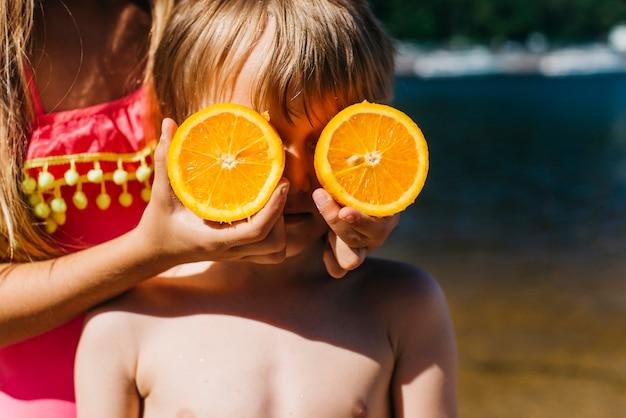 Niños pequeños jugando con naranja en la playa Foto gratis