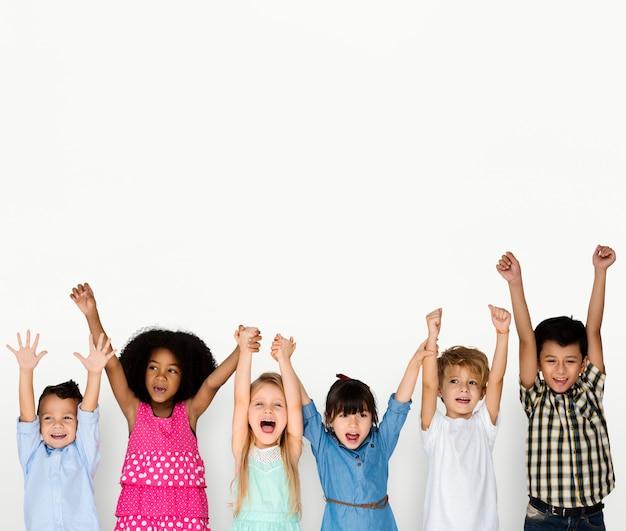 Niños pequeños manos arriba felices Foto Premium