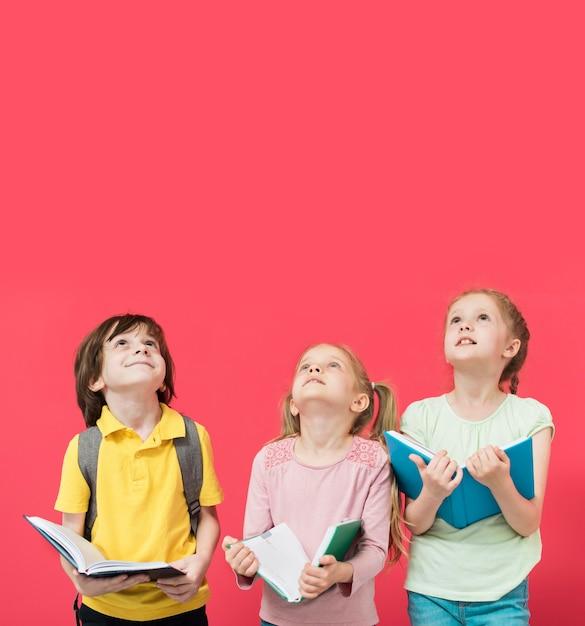 Niños pequeños mirando hacia arriba juntos Foto gratis