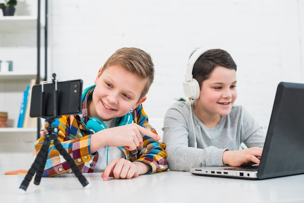 Niños con portátil y smartphone Foto gratis