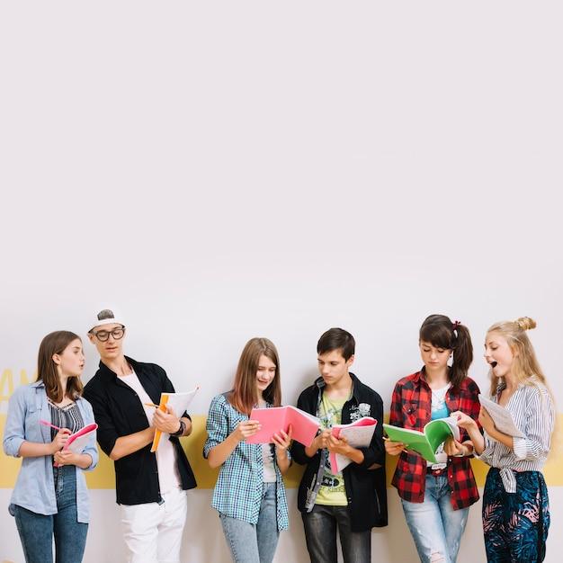 Niños que aprenden con los libros en la pared Foto gratis