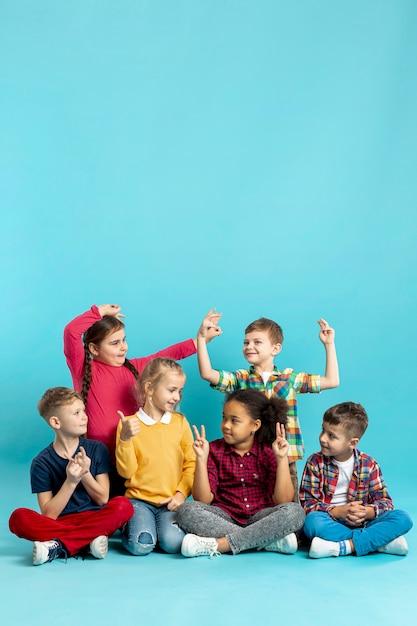 Niños que muestran diferentes signos Foto gratis