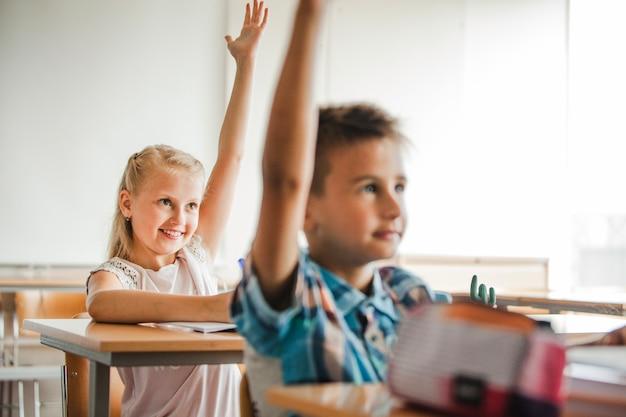 Niños que se sientan en los escritorios de la escuela que levantan las manos Foto gratis