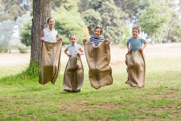Niños que tienen una carrera de sacos en el parque | Foto Premium