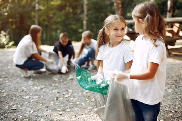 Los niños recogen basura en bolsas de basura en el parque Foto gratis