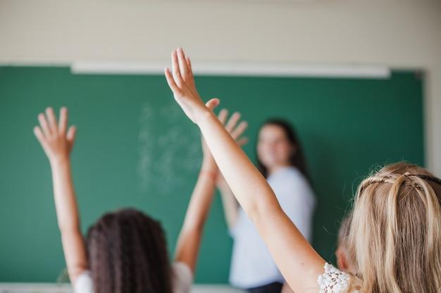 Niños en el salón de clase levantando las manos Foto gratis