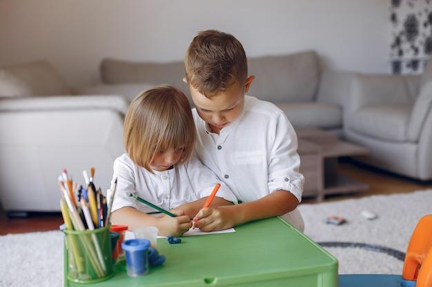 Niños sentados en la mesa verde y dibujando Foto gratis