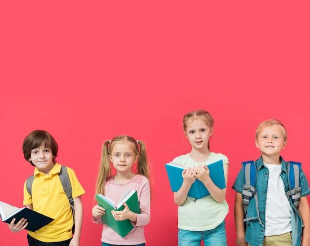 Niños sosteniendo sus libros con fondo rojo. Foto gratis