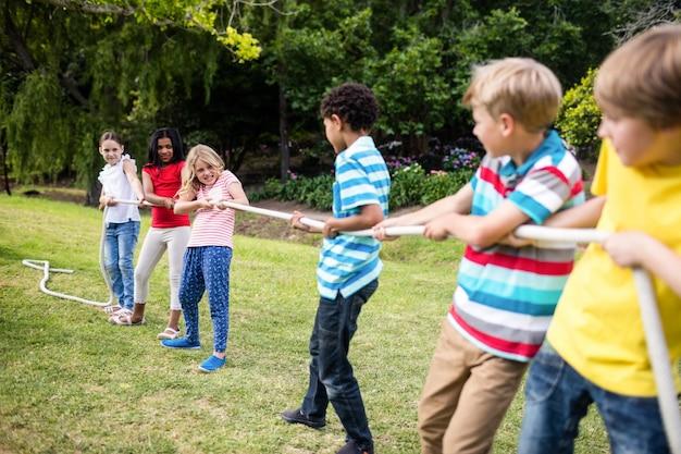 Niños tirando de una cuerda en tira y afloja Foto Premium