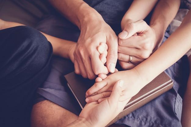 Los niños tomados de la mano y orando con sus padres en casa, la ...