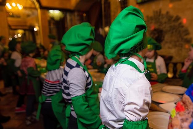 Niños en trajes verdes de cocineros y gorras verdes están en fila. Foto Premium