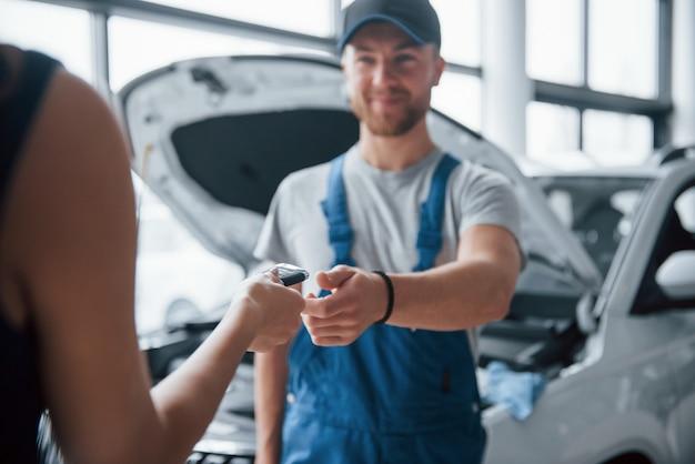 No se preocupe, todo saldrá bien. mujer en el salón del automóvil con empleado en uniforme azul tomando su auto reparado Foto gratis