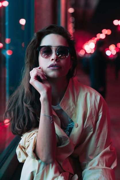 Noche en la ciudad, hermosa mujer entre luces rojas. Foto gratis