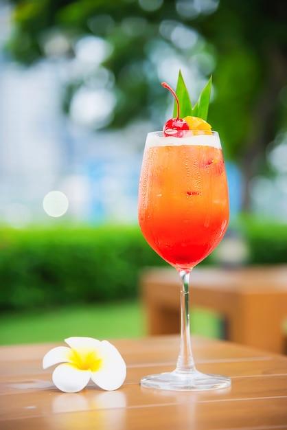 El nombre de la receta del cóctel mai tai o mai thai cóctel mundial incluye ron, jugo de limón, jarabe de orgeat y licor de naranja - bebida alcohólica dulce con flor en el jardín, concepto de vacaciones de relax Foto gratis