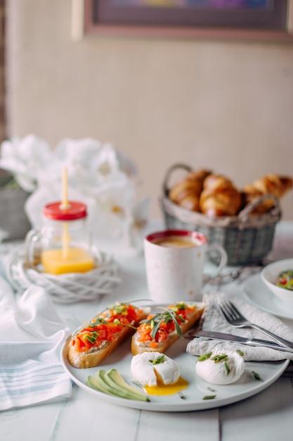 Noruega desayuno. tostadas con salmón, huevos cocidos en una mesa de madera blanca con ensalada, café, zumo de naranja y cruasanes. Foto Premium