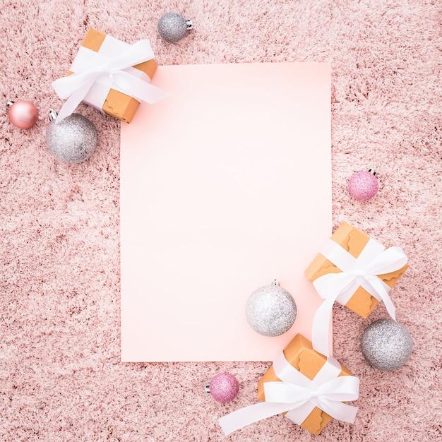 Nota en blanco con adornos navideños en una alfombra con textura rosa Foto gratis