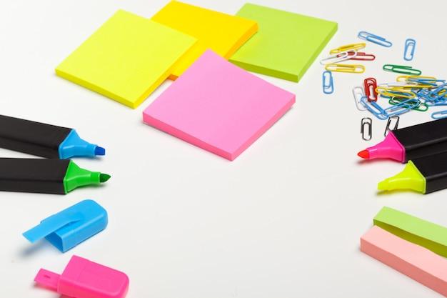 Notas adhesivas con marcadores, bolígrafos de colores, clips de papel sobre una mesa Foto Premium