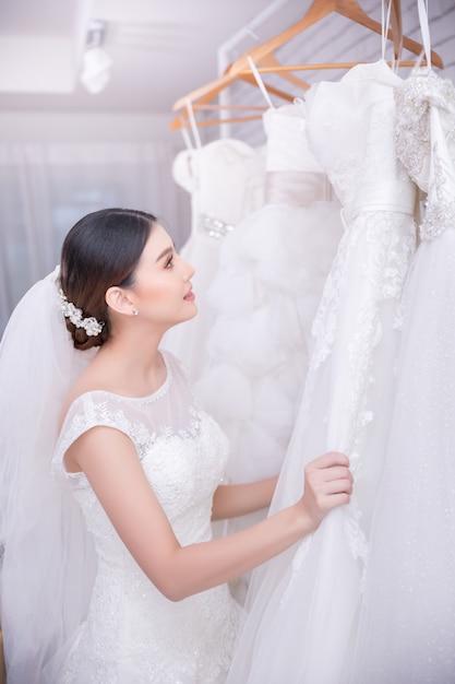 Novia asiática de la mujer joven que intenta en el vestido de boda en la boda moderna Foto gratis