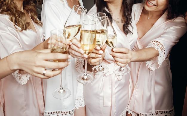 La novia y las damas de honor se colocan en túnicas de seda con gafas de champa. Foto gratis