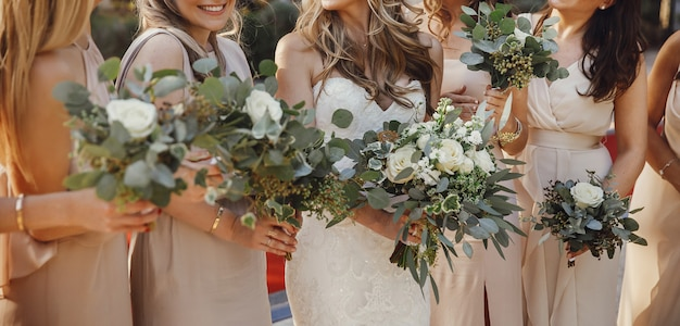 La novia y las damas de honor con los ramos de colores pastel se ponen de pie Foto gratis