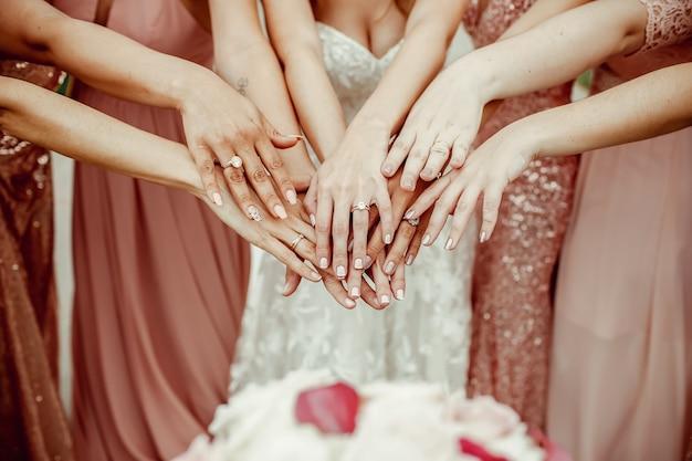 Novia y damas de honor en vestidos de color rosa enriquecen sus manos con Foto gratis