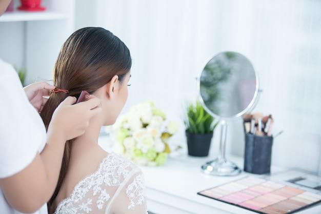 La novia hace el cabello con vestido Foto gratis
