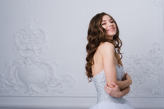 Novia hermosa joven que se coloca en el diseño ornamental interior antiguo hecho con molduras. Foto Premium
