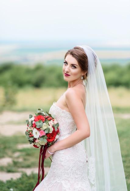 la novia hermosa en el vestido blanco con clase presenta con el ramo