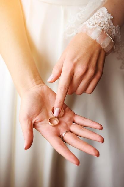 Novia hermosa en un vestido de boda que se sostiene en la palma del anillo, primer. Foto Premium