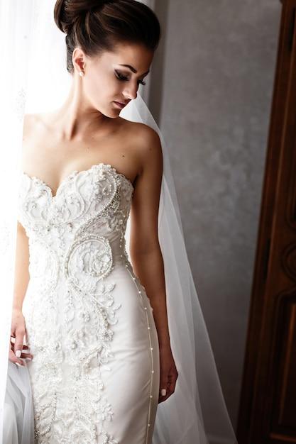 la novia en el hermoso vestido de novia con crystls y perlas se