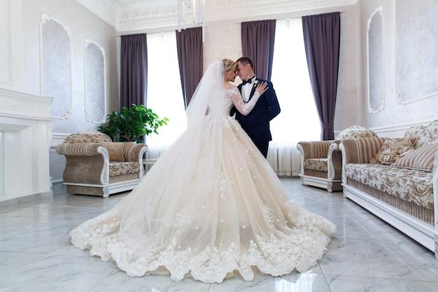 Novia y el novio abrazando suavemente en el interior en un elegante interior. concepto de escarda Foto Premium