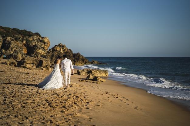 La novia y el novio caminando en la playa de arena Foto gratis