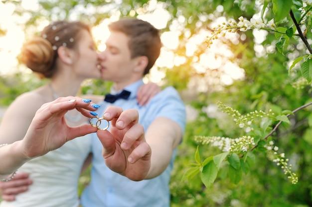 Novia y novio sosteniendo anillos y beso Foto Premium