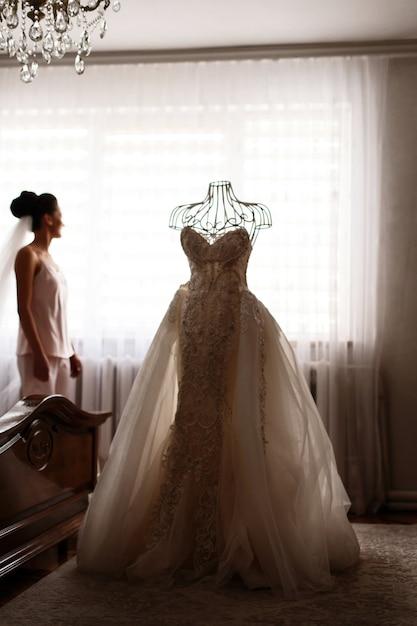 la novia está parada antes del maniquí con el vestido de boda