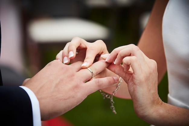 Novia poniendo el anillo de bodas en el dedo de un novio Foto Premium