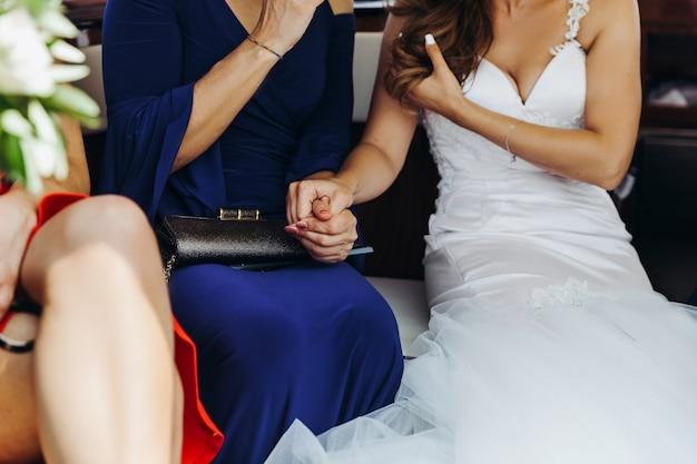 La novia sostiene la mano de la mujer sentada en la mesa. Foto gratis