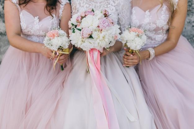 la novia y sus amigas en vestido rosa con ramos de flores en la boda