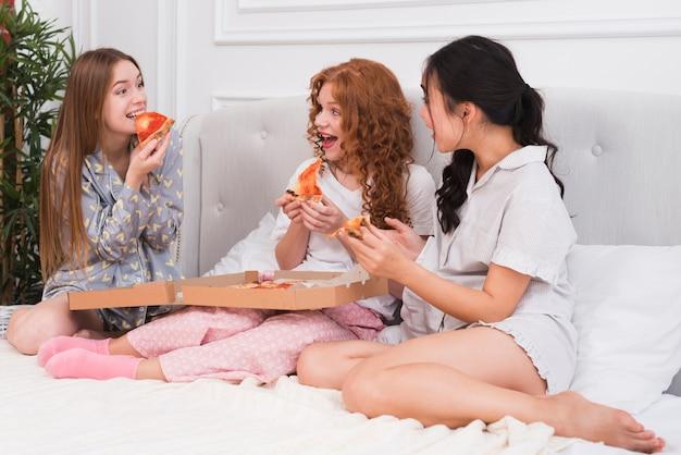 Novias de alto ángulo comiendo pizza Foto gratis
