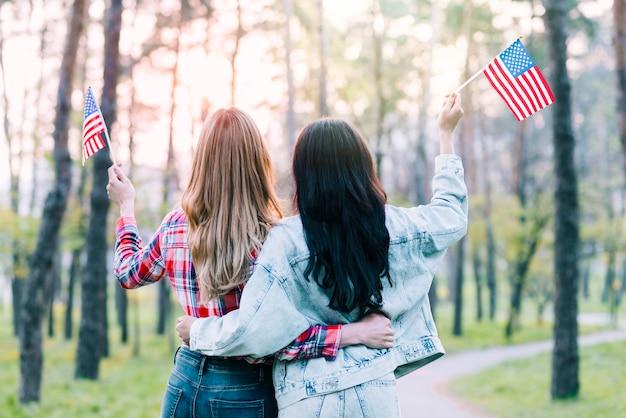 Novias con pequeñas banderas americanas abrazando al aire libre Foto gratis