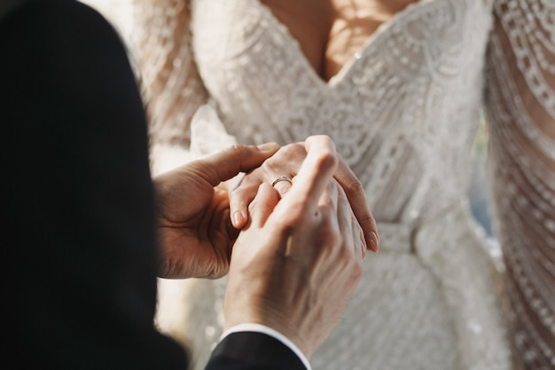 El novio lleva un anillo de bodas en el dedo de la novia Foto gratis