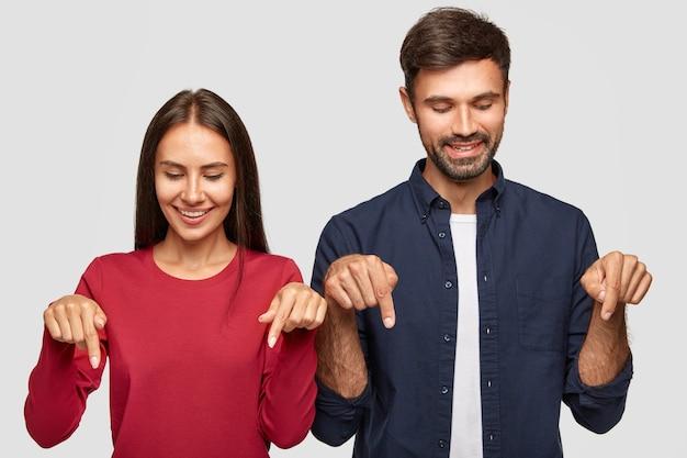 Novio y novia joven positiva con expresión alegre, notar algo agradable hacia abajo, señalar con ambos dedos índices Foto gratis