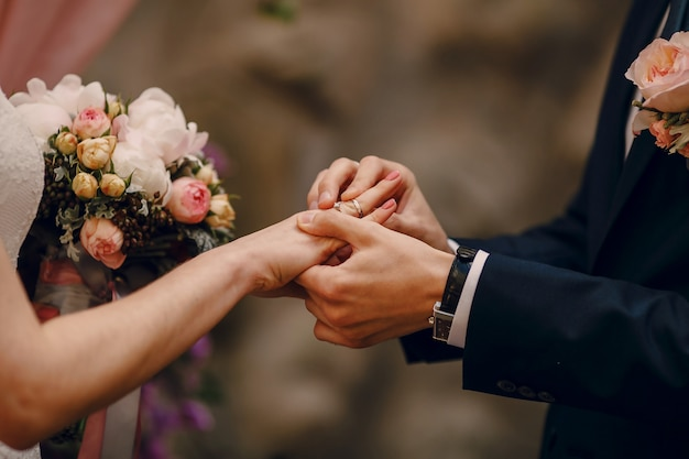 Novio poniendo el anillo en el dedo de la novia Foto gratis