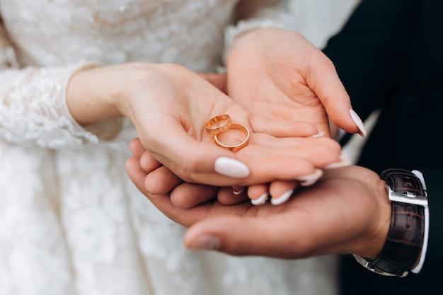 Novio toma las manos de la novia, donde hay dos anillos de boda Foto gratis