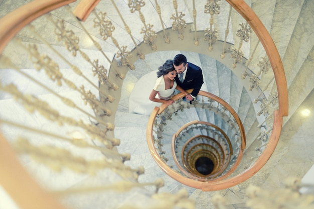 novio y novia en una escalera de espiral foto gratis