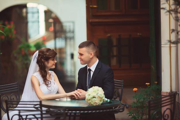 Novios enamorados hermosa novia en vestido blanco y velo y ramo de novias con novio guapo en traje azul sentado en la cafetería. retrato de cuerpo entero de hombre y niña. concepto de boda Foto Premium