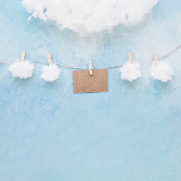 Nubes blancas y tarjeta marrón cuelgan de una cuerda con pinzas para la ropa Foto gratis