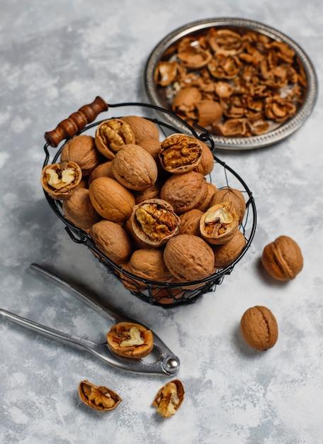 Nueces enteras con cáscara en una canasta de metal para alimentos, nueces. vista superior sobre hormigón Foto gratis