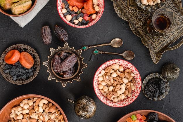 Nueces; frutos secos y dátiles en metálico; cucharas y tazón de cerámica sobre fondo negro Foto gratis