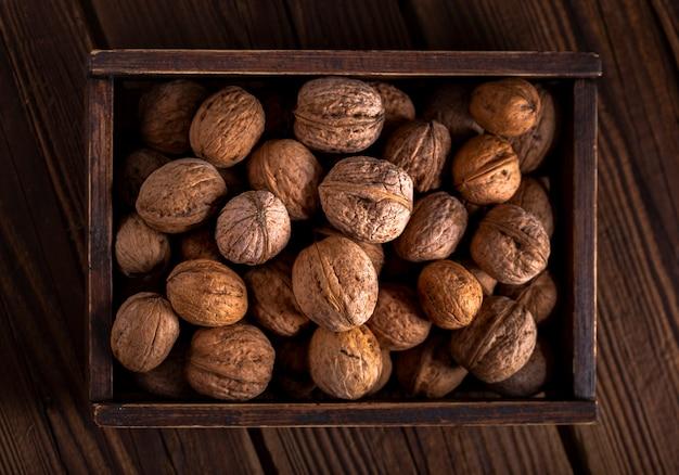 Nueces planas en caja de madera Foto gratis